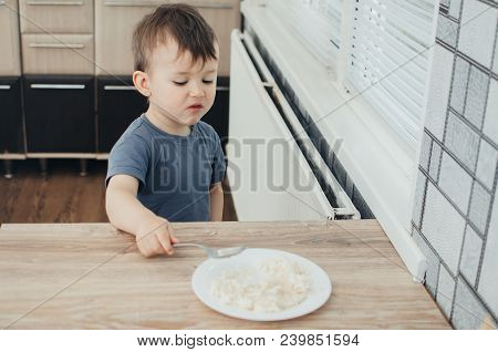 The Little Boy In The Kitchen Eagerly Eating Rice With A Spoon Independently