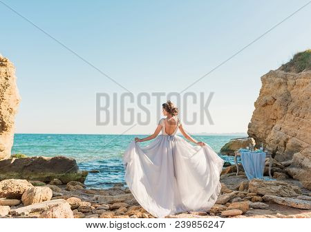 Beautiful Bride In Luxury Wedding Dress With Bouquet At The Sea Side. Cheerful Bride Dancing. Just M