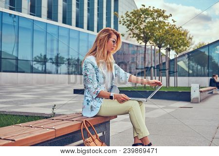 Stylish Fashion Blogger Relaxing Outdoor, Working On The Laptop, Sitting On A Bench Against A Skyscr