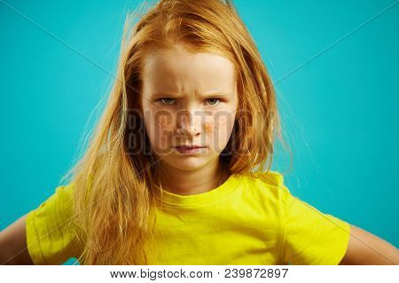 Portrait of disgruntled child girl with furrowed eyebrows, expressing dissatisfaction or disagreement, demonstrates difficulty of character and capricious mood, stood upset kid on blue isolated background. Concept of relationships and mutual understanding poster
