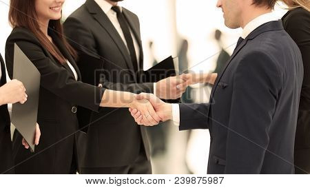 Close-up Of Business Partners Shaking Hands After Signing Of The Contract Against The Background Of