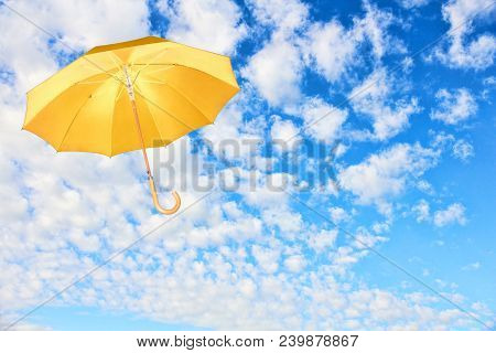 Yellow Umbrella Flies In Sky Against Of White Clouds.wind Of Change Concept.mary Poppins Umbrella.