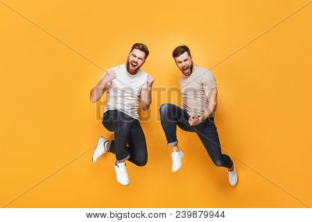 Two young cheerful men jumping together and celebrating isolated over yellow background