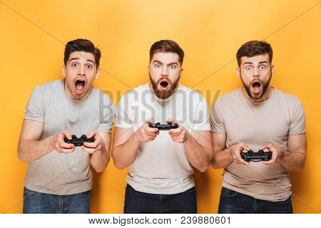 Three young shocked men holding joysticks while playing video games isolated over yellow background