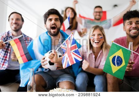 Young Group Of Friends Watching Sport On Television And Cheering