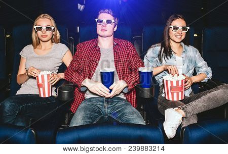 Young People Are Sitting In Chairs In Cinema. They Wear Glasses For Watching Movies. Guy Has Cup Of