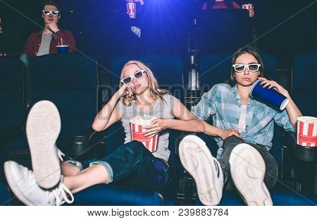 Cool And Relaxed Girl Are Sitting In A Front Row And Watching Movie. They Have Put Their Legs Up. Al