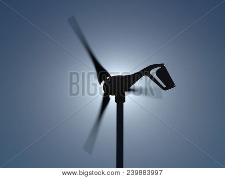 An Electric Wind Generator Backlit By The Sun. The Blades Are Blurred From Spinning At High Speed.