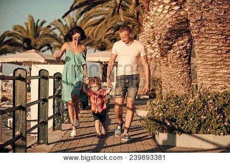 Happy Family Spend Time Together, Urban Background. Parents With Son Walking Near Palm Trees, Happy