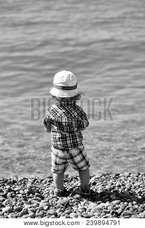 Baby Boy Cute Fair-haired Blond Kid Tiny Little Child Wearing Checked Shirt Shorts And White Hat Sta