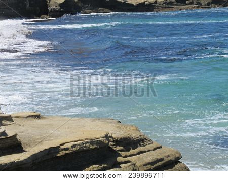 Solid Rock Shoreline At Lower Tide With A Beautiful Backdrop Of The Pacific Ocean