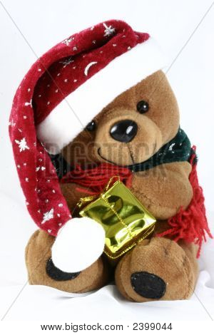 Teddy Bear Holding Its Red Hat And Looking At A Christmas Present