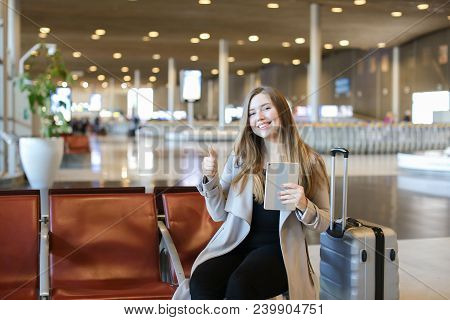 Young Woman Browsing By Modern Tablet In Airport Waiting Room And Sitting Near Grey Valise, Showing