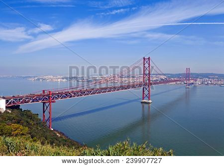 Ponte 25 de Abril Bridge in Lisbon, Portugal. Connects the cities of Lisbon and Almada crossing the Tagus River. View from Almada with Lisbon across the river.
