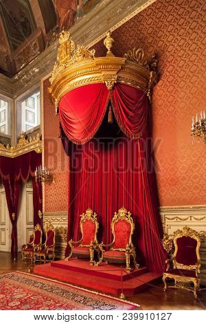 Lisbon, Portugal - June 10, 2013: Gold and Red King and Queen thrones under a baldachin in the Throne Room of Ajuda National Palace or Palacio Nacional da Ajuda. 19th century neoclassical Royal Palace