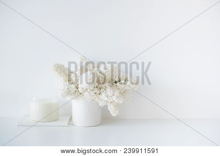 Minimalist White Home Decor, Fresh Lilac Flowers Bouquet In Vase And Candle On Table And Empty Wall