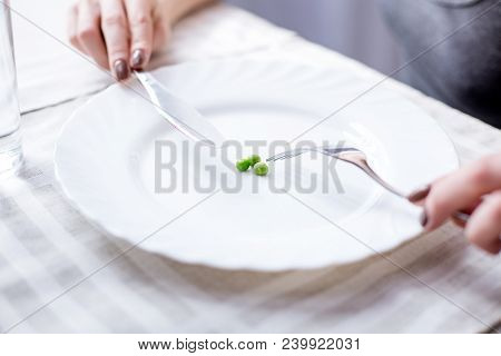 Small Portion. Close Up Of A Plate With Peas Standing On The Table