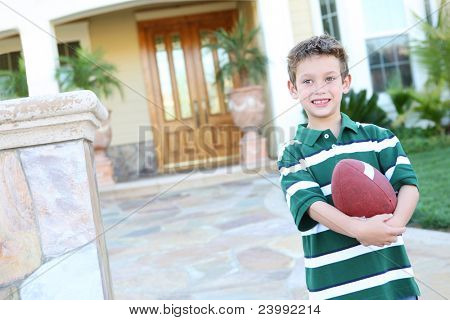 A young boy outside home holding football having fun