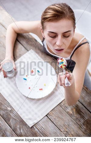 Serious Illness. Sad Pale Woman Taking A Spoon Of Pills While Being Seriously Ill