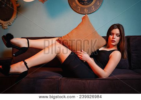 Young Attractive Sexy Woman Sitting On Sofa And Legs Up, Holding Pillow And Looking In Floor With So