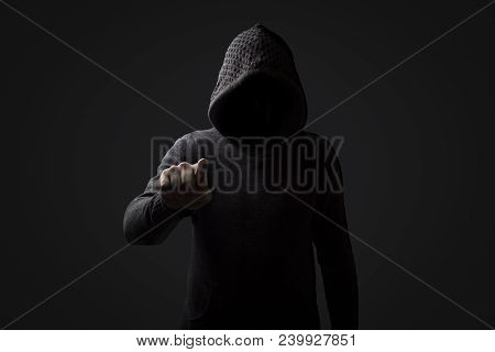 Faceless Man In A Hood With Points A Finger At The Viewer On A Dark Background. Concept Threats And