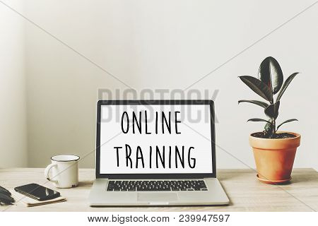 Online Training Text On Laptop Screen On Wooden Desktop With Phone, Notebook, Coffee And Plant. Busi