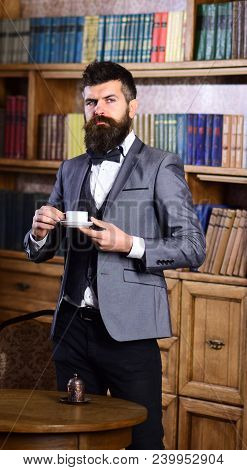 Lawyer Stands In Luxury Interior With Cup Of Tea Or Coffee. Bearded Man In Expensive Suit In His Cab