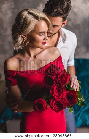 Handsome Man Hugging Smiling Sensual Woman In Red Dress Holding Beautiful Roses