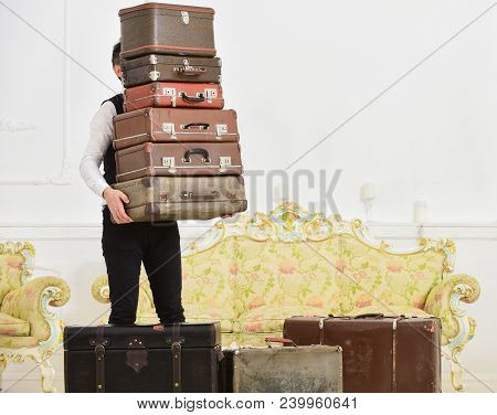 Butler And Service Concept. Macho, Elegant Porter Carries Heavy Pile Of Vintage Suitcases. Man With