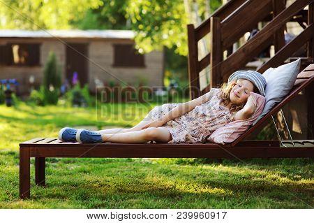 child girl relaxing on sunbed in sunny garden, enjoying summer vacations outdoor
