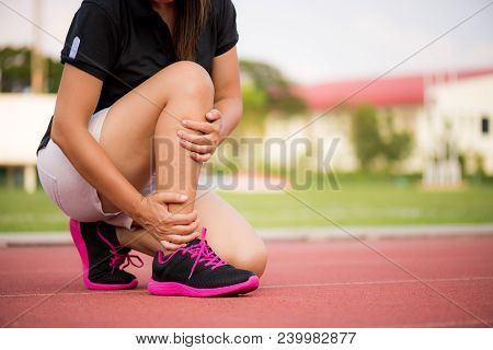 Ankle Sprained. Young Woman Suffering From An Ankle Injury While Exercising And Running On Running T
