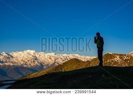 Adventure, With Cup Of Coffee, Is Standing On The Mountain Slope, Admiring The Stunning Mountain Ran