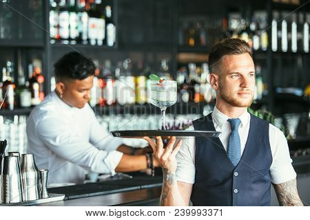 Elegant Waiter Is Holding A Tray With A Decorated Cocktail Ready To Serve With A Concentrated Mixed
