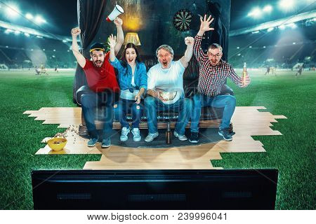 Ardent Fans Are Sitting On The Sofa And Watching Tv In The Middle Of A Football Field. Football Conc