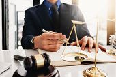 law and justice concept, Attorney or lawyer judgement lawsuit with holding pen, law book,gavel and scales of justice at table in office. poster
