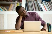 Tired African American office worker massaging neck suffering from chronic muscular pain sitting long hours in uncomfortable position. Concept of incorrect posture, inactive sedentary lifestyle poster