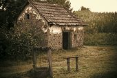 House barrack with old well in yard. Rural lifestyle, countryside. Decay, decline, ruins. Architecture, structure, construction Village with abandoned building vintage filter poster