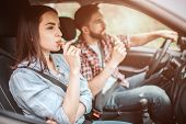 Couple is sitting in car. Guy is driving and eating candy bar. Girl is looking straight and biting a piece of bar as well. They are safety locked with seatbelt poster