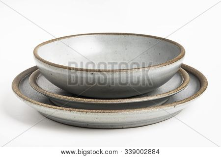 A Set Of Stoneware Dinner Service With Different Plates And Bowls On A White Plain Background.