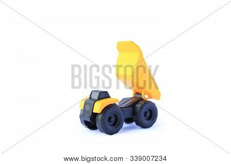 The Yellow Toy Car Heavy Truck Isolated On White Background. Children's Tractor Toy. Wheel Loader Co