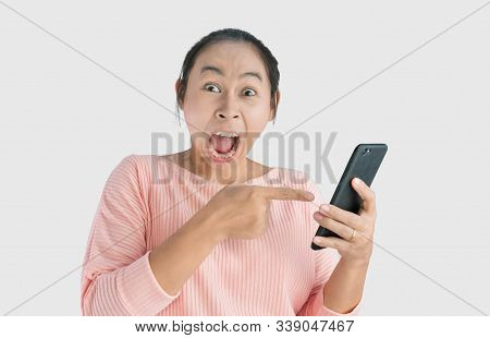 Asian Woman Angry And Yelled What She See In The Smartphone And Pointing It, Isolated On White Backg
