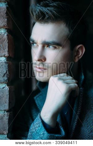 A close up portrait of a thoughtful fashionable young man near the brick wall. Casual fashion for men.