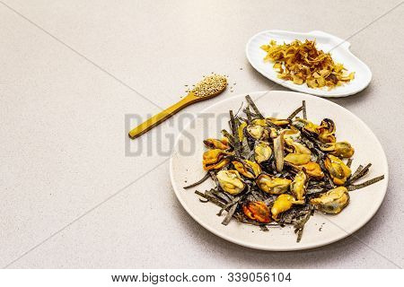 Mussels with nori seaweed, sesame and tuna bonito flakes. Superfood concept. Healthy vegetarian eating. Ceramic plate, stone concrete background poster