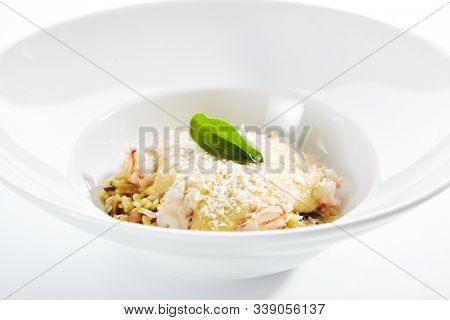 Macro shot of risotto with mussels and shrimps on white restaurant plate isolated. Delicious traditional prepared italian seafood paella with prawns, squid, mussels, cheese and greens close up