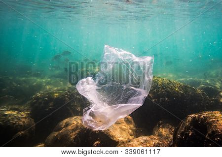 A Shredded Plastic Bag Drifting Under The Surface Of A Blue, Tropical Ocean. Bad Ecology Of Sea Wate