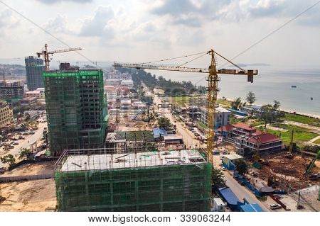 Construction High-rise Building By Crane In City Near Sea. Construction Of Expensive Hotels In Resor