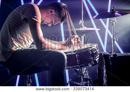 Pensive Man Playing The Drums, Playing The Drums With Sticks Close-up. Against The Background Of Col