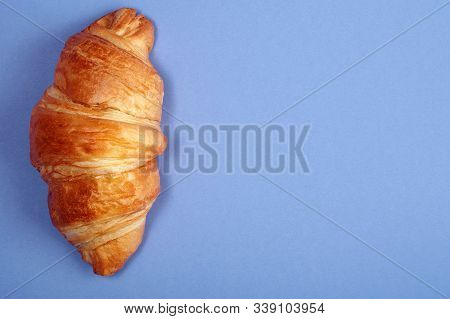 Croissant Top View. Croissant On Bright Blue Background. Fresh Ruddy Croissant On Color Cardboard.