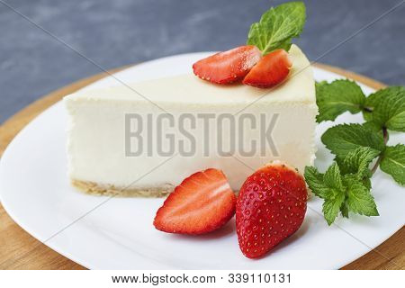 Classic Cheesecake New York Sliced Piece Of Cheesecake With Fresh Strawberries And Mint On A White P
