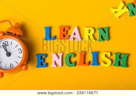 Word Learn English Made With Wooden Letters On Orange Desk Litle Clock. Concept Of English Language